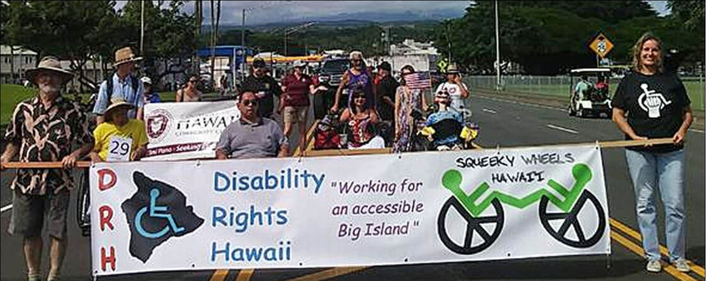A picture of about 15 DRH members marching in the November 10, 2018, Veterans Day Parade in Hilo. A banner is being carried at the front of the marchers announcing Disability Rights Hawaii (DRH) and the Facebook group named Squeaky Wheels Hawaii. Logos representing the two groups are printed on the banner (an outline map of Hawaii County with a wheelchair symbol inside it) and Squeaky Wheels (two wheelchairs facing each other, each performing a wheelie). Many of the members are marching with wheelchairs.